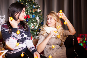 Two good female friends next to a decorated christmas tree having fun and playing with garlands