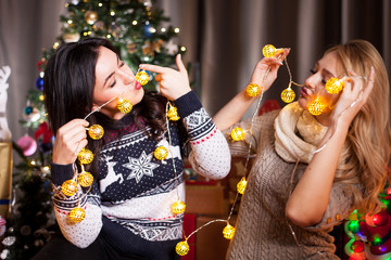 Smiling and having fun. Two girls in christmas decorated room in christmas eve spending quality time together