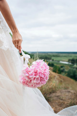 body parts. Hand of a young girl, a bride in a wedding dress. Holds a flower of a pink hydrangea.