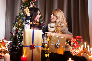 Happy friends with big gift boxes in Christmas decorated room having fun