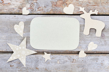Christmas paper ornaments and empty paper. Cut out paper New Year decorations of deer, stars, hearts, blank sheet of paper on old wooden background.