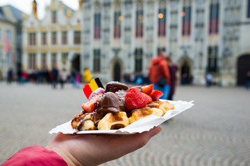 Belgium waffle with chocolate sauce and strawberries, Bruges city background