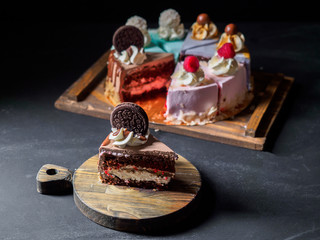 Set of pieces cakes on black background
