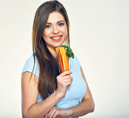 Smiling girl holding glass with carrot.