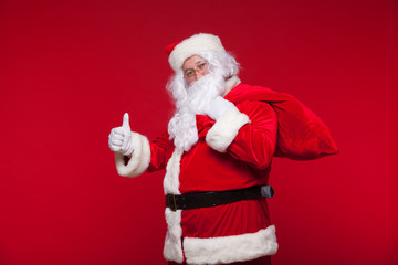 Christmas. santa claus with big bag on shoulder is on red background