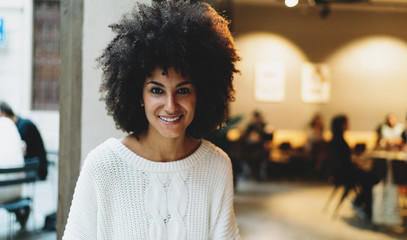 Half length portrait of a beautiful afro american female with afro hair style wearing casual clothes smiling at the camera while sitting on a blurred city  coffee shop background on a weekend.