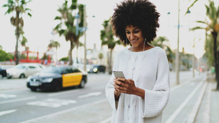 Model look woman tracking the taxi called by a mobile phone app. Smiling entrepreneur chatting online while relaxing outdoors with a music downloaded and played on a smartphone.