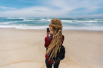 Young woman with blond dreadlocks takes the picture of the ocean on a smartphone.