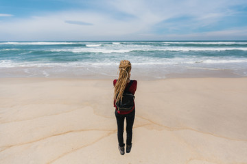 Young woman with blond dreadlocks stands on the shore of the ocean.