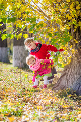 Two cute girls peek out from behind the tree. Two sisters are in the autumn park.