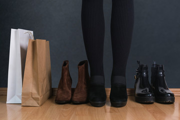 Woman standing by the shopping bags and shoes