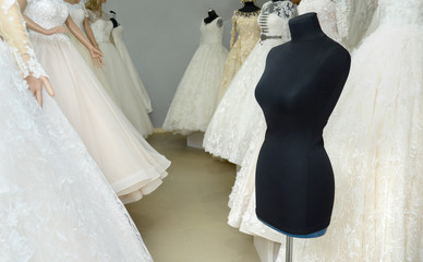 black mannequin in the background of the wedding dresses
