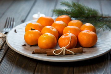 a plate of tangerines stay on the wooden table. new year concept