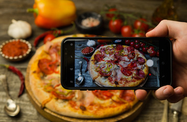 Man taking photo of pizza on smartphone
