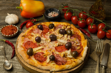 Pizza with pepperoni, bacon, chicken on dark wood background. Hot homemade delicious pizza