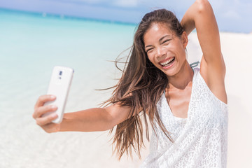 Selfie summer beach vacation fun girl laughing. Happy Asian woman taking self-portrait pictures with mobile phone on tropical holidays in Caribbean posing for camera.