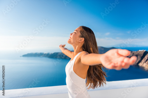 Wall mural Europe cruise destination Santorini Greece travel vacation carefree woman enjoying freedom with open arms in famous travel holiday. Elegant Asian girl on greek travel luxury resort in Oia Santorini.