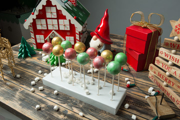 Cake pops on christmas decorated wooden table