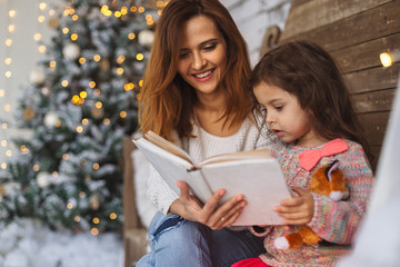 Mother and daughter reading on Christmas eve