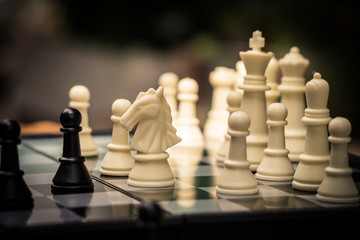 Chess pieces on the black and white board. Black pawn are leader to fight with teamwork to victory.