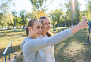 Beautiful girls taking a selfie with a phone.