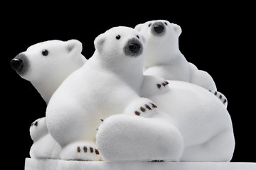 Christmas and New Year decorations: figurines of a white polar bear with cubs. Isolated, black background.
