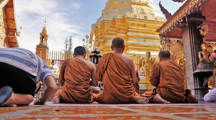 Monks sitting and praying in front of temple in Thailand