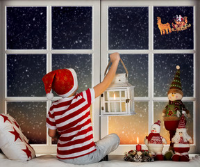 Merry Christmas and happy holidays!  Little boy sitting  on the window and looking at Santa Claus flying in his sleigh against moon sky.  Room decorated on Christmas.