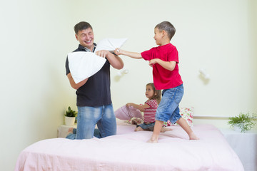 Family Concepts and Ideas. young Caucasian Family Having a Playful Funny Pillow Fight Indoors.