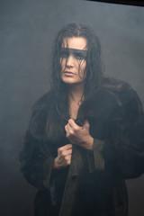 Cyberpunk female with wet hair in fog, painted eye mask