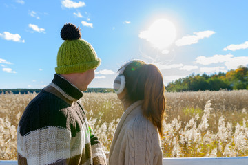 Young happy couple looking at distance against scenic view of autumn bullrush field