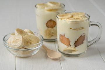 Freshly made banana pudding in the circles and the slices of banana on a white table.