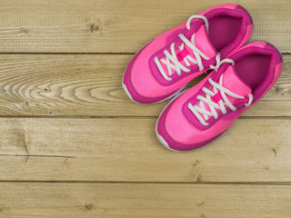 Beautiful pink women's running shoes vintage on the floor. The view from the top.