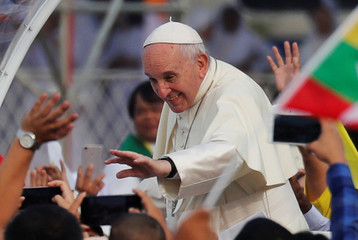 Pope Francis waves to Catholic faithful as he arrives to lead a mass at Kyite Ka San Football Stadium in Yangon, Myanmar