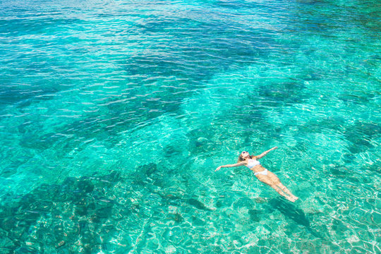 Young woman swimming in the beautiful blue sea. Overhead view. Aerial shot.
