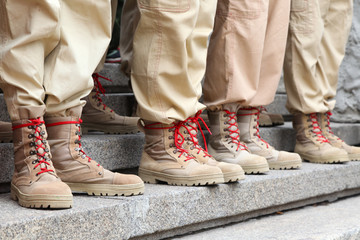 Legs in beige sand color footwear army boots