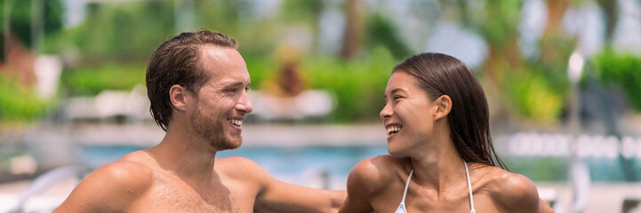 Wall Mural - Happy couple having talking at luxury resort hotel travel beach holiday together on summer vacation. Asian woman, man relaxing by swimming pool