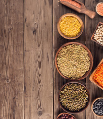 Set of various beans and colorful lentils in bowls and box on wooden background, top view with copy space