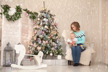 Pretty Slim Mother Wearing Bright Knitted Sweater and Blue Jeans Playing With Her Little Baby Near The Decorated Christmas Tree with New Year Gift Boxes. Real Family.
