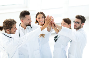 group of doctors giving each other a high five.