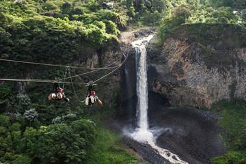 Tourists gliding on the zip line trip against Bridal veil (Manto de la novia), waterfall in Cascades route, Banos, Ecuador