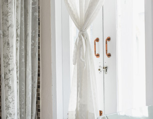 White lace curtain with copper window handles in bathroom interior