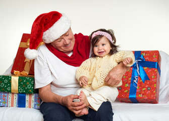 Grandma and granddaughter dressed in santa hat with gift boxes sit on sofa, white background. New year eve and christmas holiday concept.