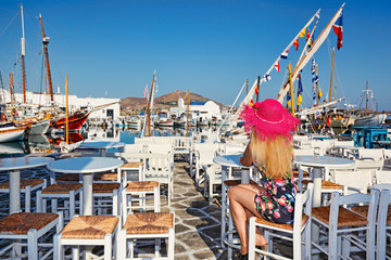 Young woman sitting at a traditional tavern in Naousa of Paros island, Greece