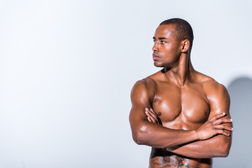 athletic shirtless african american sportsman looking away isolated on grey