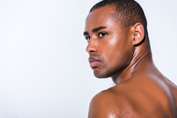 portrait of handsome shirtless african american sportsman looking away isolated on grey
