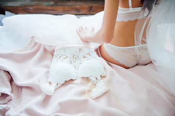 bride with long dark curls holds wedding dress