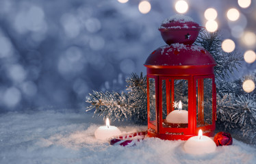 Christmas decorated lantern and candles on snow with copy space