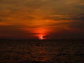 sunset last light of sun on horizontal line over dark sky