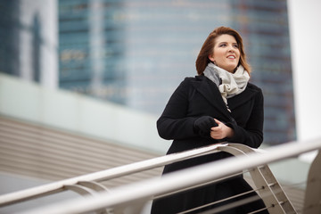 Photo of smiling woman in black coat and scarf on blurred background